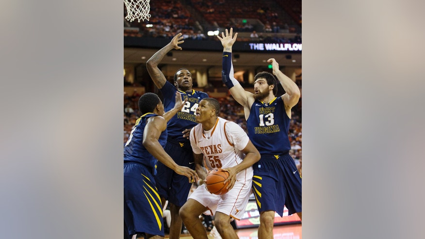 Texas' Cameron Riley (55) is pressured by West Virginia's Aaric Murray (24) and Deniz Kilicli (13) as he tries to shoot during the first half of their NCAA college basketball game, Wednesday, Jan. 9, 2013, in Austin, Texas. (AP Photo/Statesman.com, Alberto Martênez)  MAGS OUT; NO SALES; INTERNET AND TV MUST CREDIT PHOTOGRAPHER AND STATESMAN.COM