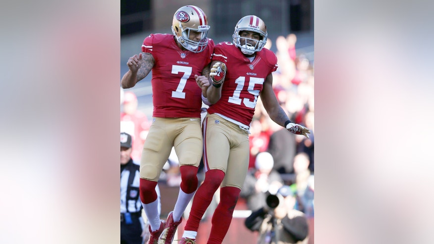 FILE - In this Dec. 30, 2012, file photo, San Francisco 49ers quarterback Colin Kaepernick (7) celebrates with wide receiver Michael Crabtree (15) after they connected on a 49-yard touchdown pass against the Arizona Cardinals during the second quarter of an NFL football game in San Francisco. This playmaking, go-to tandem is on quite a roll for the 49ers, and they are determined to keep it that way right into February. Crabtree looks to carry his career season into the next phase: Saturday night's NFC divisional playoff game against Green Bay.(AP Photo/Marcio Jose Sanchez, File)