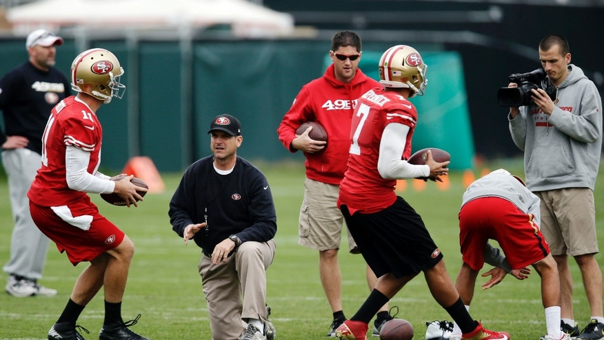 San Francisco 49ers head coach Jim Harbaugh, center, instructs quarterback Alex Smith, left, and quarterback Colin Kaepernick (7) during NFL football practice in Santa Clara, Calif., Wednesday, Jan. 9, 2013. The 49ers are scheduled to host the Green Bay Packers in an NFC divisional playoff game Saturday. (AP Photo/Marcio Jose Sanchez)