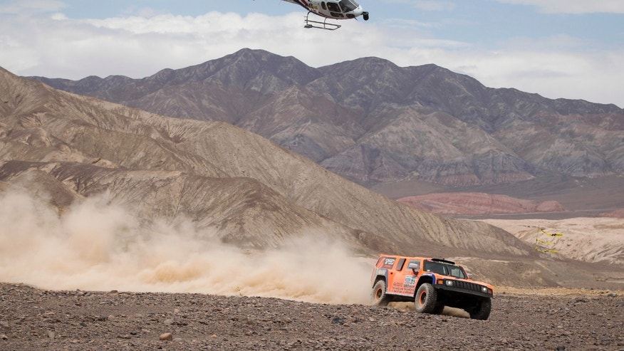 A TV helicopter follows Robby Gordon and co-driver Kellon Walch of the U.S. as they compete in their Hammer during the 6th stage of the 2013 Dakar Rally from Arica to Calama, Chile, Thursday, Jan. 10, 2013. The race finishes in Santiago, Chile, on Jan. 20. (AP Photo/Victor R. Caivano)