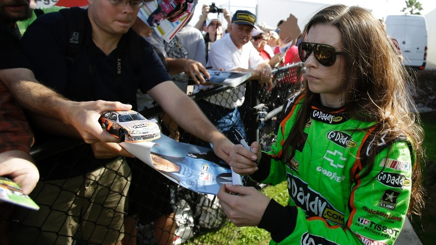 Driver Danica Patrick, right, signs autographs for fans after the morning session of NASCAR auto race testing at Daytona International Speedway, Thursday, Jan. 10, 2013, in Daytona Beach, Fla. (AP Photo/John Raoux)