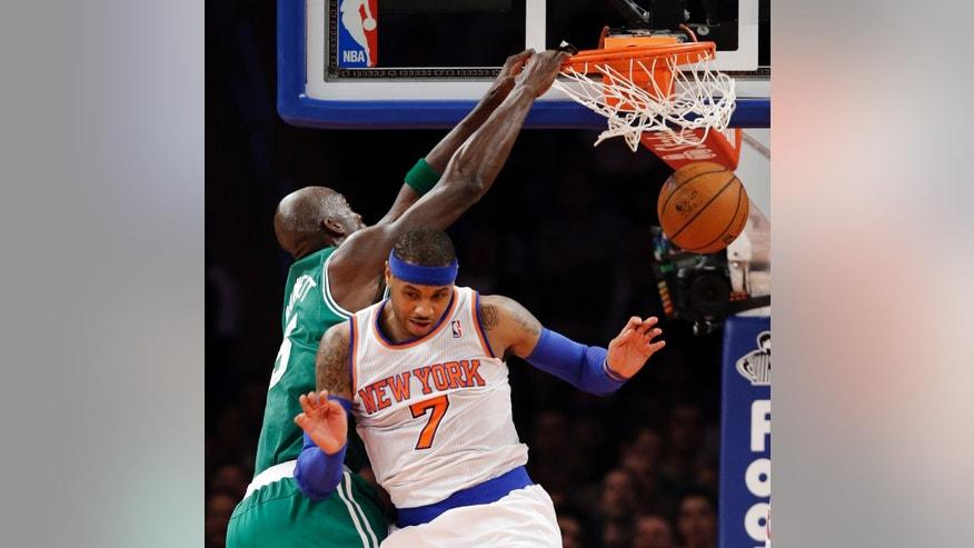 Boston Celtics forward Kevin Garnett (5) dunks against New York Knicks forward Carmelo Anthony (7) in the first half of their NBA basketball game at Madison Square Garden in New York, Monday, Jan. 7, 2013. (AP Photo/Kathy Willens)