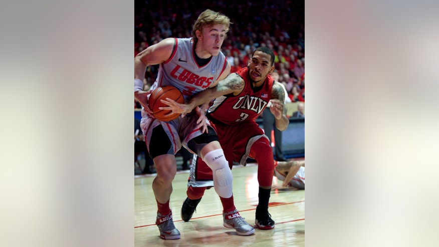 New Mexico's Hugh Greenwood, left, tries to score against the defense of UNLV's Anthony Marshall during the first half of an NCAA college basketball game on Wednesday, Jan 9, 2013, in Albuquerque, N.M. (AP Photo/Eric Draper)