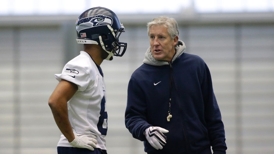 Seattle Seahawks head coach Pete Carroll, right, talks with wide receiver Golden Tate during NFL football practice, Wednesday, Jan. 9, 2013, in Renton, Wash. The Seahawks play the Atlanta Falcons on Sunday in an NFC divisional playoff game in Atlanta. (AP Photo/Ted S. Warren)