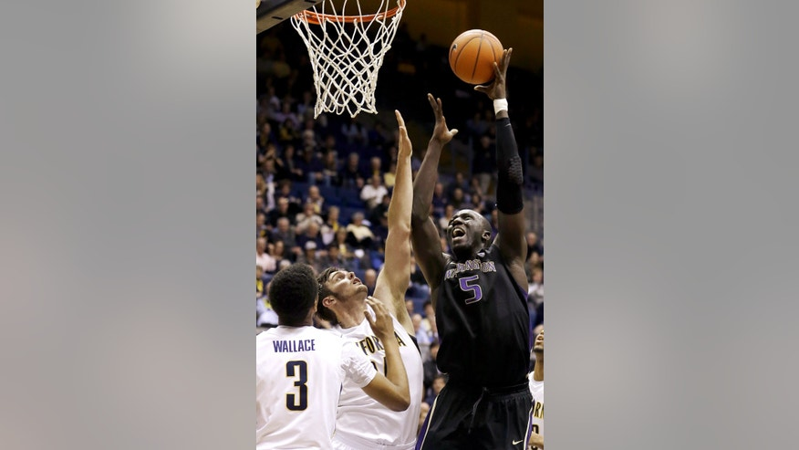 Washington center Aziz N'Diaye (5) shoots against California guard Tyrone Wallace (3) and forward Robert Thurman (34) during the first half of an NCAA college basketball game in Berkeley, Calif., Wednesday, Jan. 9, 2013. (AP Photo/Jeff Chiu)
