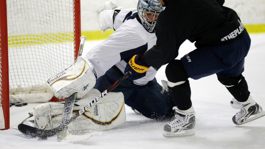 Buffalo Sabres goalie Ryan Miller makes a save on a shot by Sabres' Ville leino (23) during an informal NHL hockey workout in Amherst, N.Y., Friday, Jan. 11, 2013. (AP Photo/David Duprey)