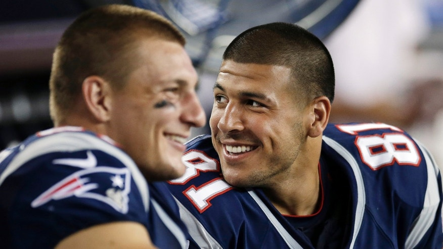 FILE - In this Aug. 9, 2012, file photo, New England Patriots tight ends Aaron Hernandez (81) and Rob Gronkowski (87) share a laugh while sitting on the bench during an NFL preseason football game against the New Orleans Saints in Foxborough, Mass. Gronkowski and Hernandez have played just five games together this season because of injuries. Now the Patriots dangerous tight ends are back and posing a major threat to the Houston Texans in Sunday's AFC divisional playoff game. (AP Photo/Elise Amendola, File)