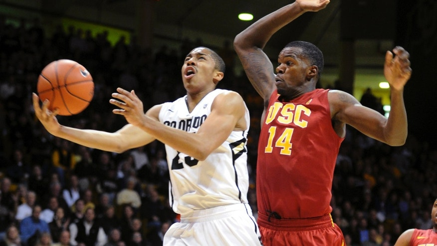 Southern California's DeWayne Dedmon (14) defends as Colorado's Spencer Dinwiddie, left, drives to the basket during the first half of their NCAA college basketball game, Thursday, Jan. 10, 2013, in Boulder, Colo. (AP Photo/The Daily Camera, Cliff Grassmick) NO SALES; MAGS OUT; TV OUT