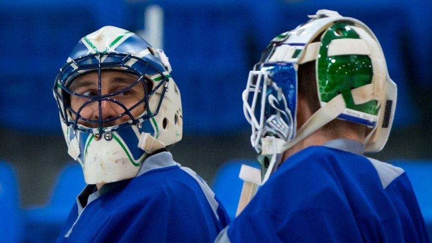 Vancouver Canucks' goalies Roberto Luongo, left, and Cory Schneider talk during an informal hockey practice at the University of British Columbia in Vancouver, British Columbia on Friday Jan. 11, 2013. (AP Photo/The Canadian Press, Darry; Dyck)