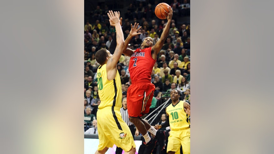 Arizona's Mark Lyons (2) shoots between Oregon's Waverly Austin, left, and Johnathan Loyd (10) during the first half of their NCAA college basketball game, Thursday, Jan. 10, 2013, in Eugene, Ore. (AP Photo/Chris Pietsch)