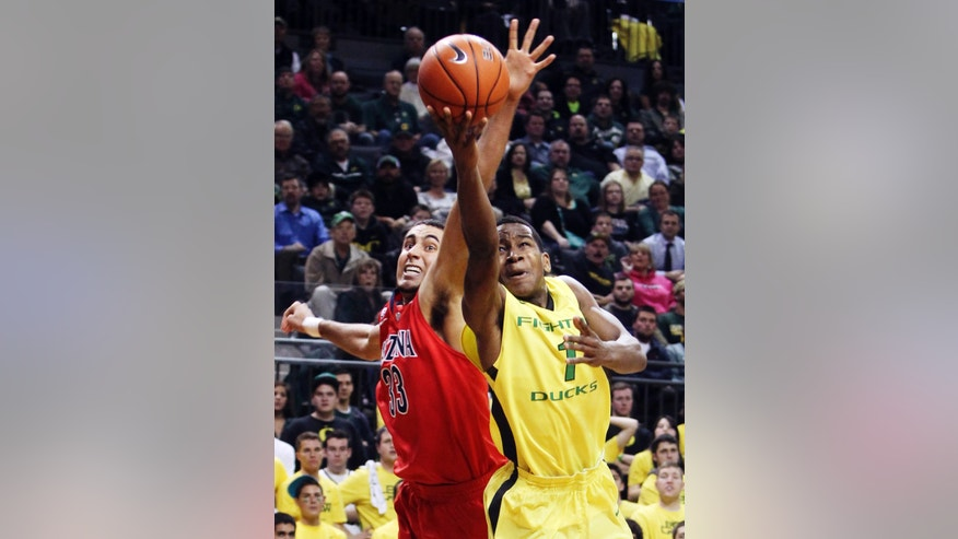 Arizona's Grant Jerrett (33) defends against a shot by Oregon's Dominic Artis during the second half of their NCAA college basketball game, Thursday, Jan. 10, 2013, in Eugene, Ore. Oregon won 70-66. (AP Photo/Chris Pietsch)