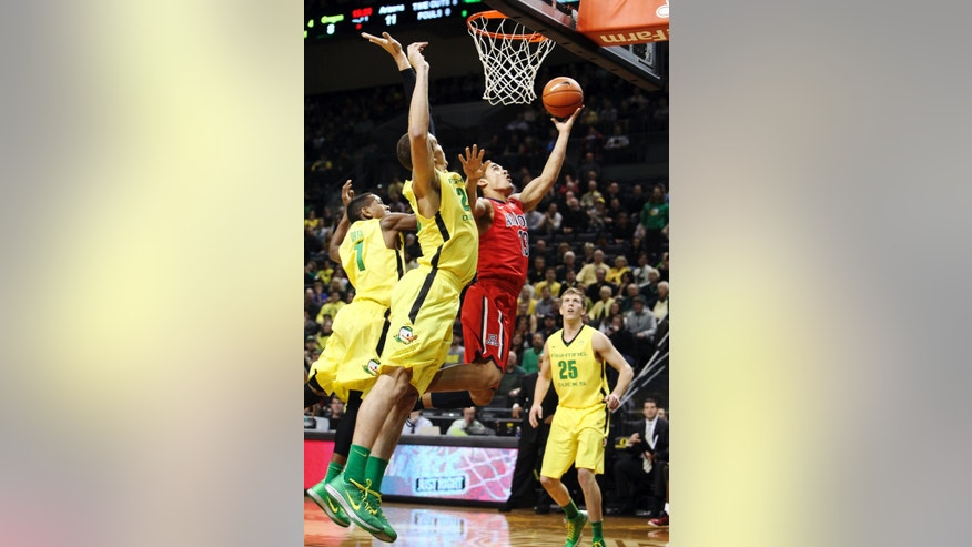 Arizona's Nick Johnson, center, drives past Oregon's Dominic Artis, left, Waverly Austin and E.J. Singler, right, during the first half of their NCAA college basketball game, Thursday, Jan. 10, 2013, in Eugene, Ore. (AP Photo/Chris Pietsch)
