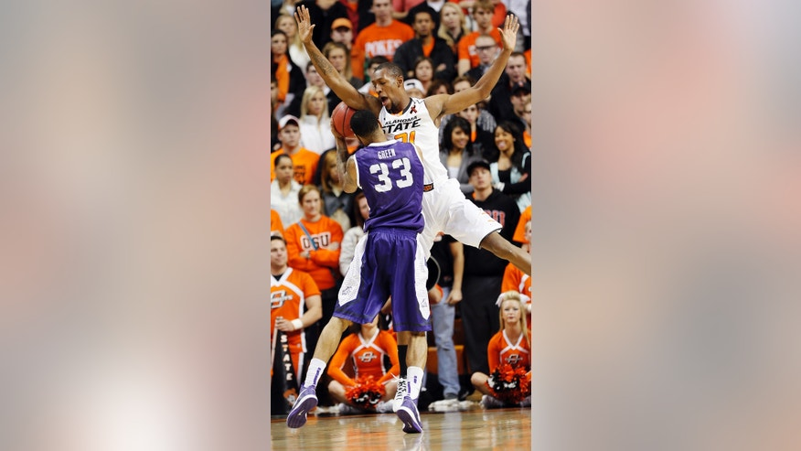 Oklahoma State's Kamari Murphy (21) defends on TCU's Garlon Green (33) during their NCAA college basketball game, Wednesday, Jan. 9, 2013, in Stillwater, Okla. (AP Photo/The Oklahoman, Chris Landsberger) LOCAL TV OUT (KFOR, KOCO, KWTV, KOKH, KAUT OUT); LOCAL INTERNET OUT; LOCAL PRINT OUT (EDMOND SUN OUT, OKLAHOMA GAZETTE OUT) TABLOIDS OUT