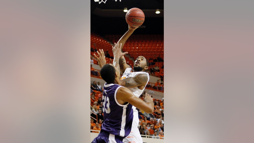 Oklahoma State's Michael Cobbins (20) shoots over TCU's Garlon Green (33) during their NCAA college basketball game, Wednesday, Jan. 9, 2013, in Stillwater, Okla. (AP Photo/The Oklahoman, Chris Landsberger) LOCAL TV OUT (KFOR, KOCO, KWTV, KOKH, KAUT OUT); LOCAL INTERNET OUT; LOCAL PRINT OUT (EDMOND SUN OUT, OKLAHOMA GAZETTE OUT) TABLOIDS OUT