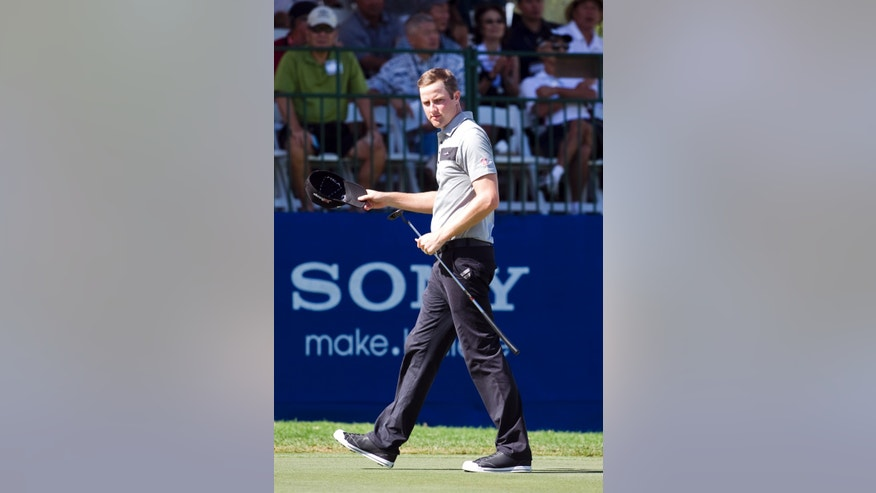 Chris Kirk walks off the 18th green after making an eagle putt during the second round of the Sony Open golf tournament, Friday, Jan. 11, 2013, in Honolulu.  (AP Photo/Marco Garcia)
