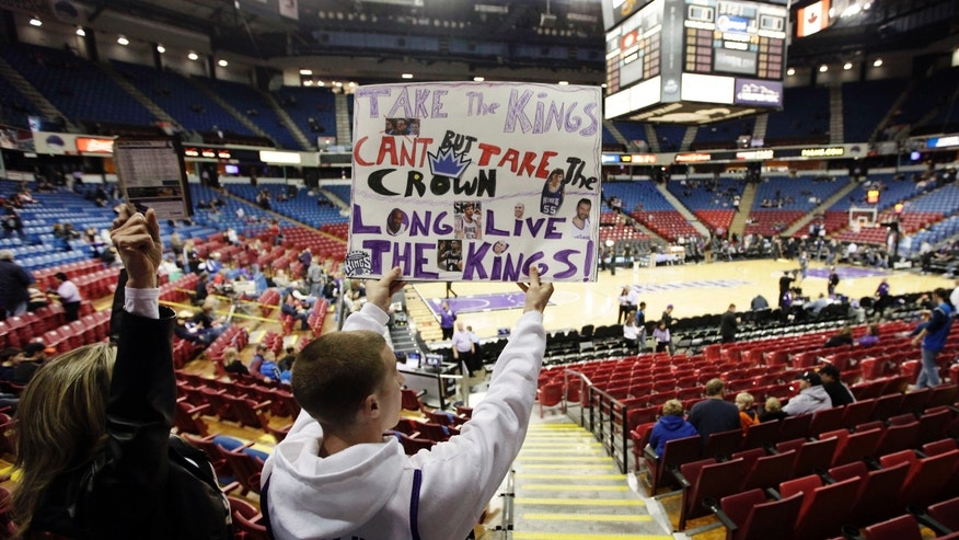 James Frazier, right, holds a sign alongside his mother Karen Roth before an NBA basketball game between the Sacramento Kings and the Dallas Mavericks in Sacramento, Calif., Thursday, Jan. 10, 2013. Word of the possible sale of the team to investor Chris Hansen who would move the franchise to Seattle has Kings fan showing their support with hopes they will remain in Sacramento. (AP Photo/Rich Pedroncelli)