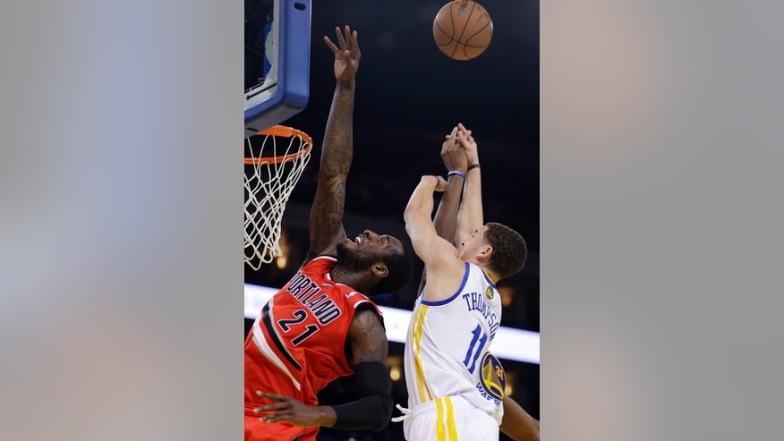 Portland Trail Blazers' J.J. Hickson, left, and Golden State Warriors' Klay Thompson (11) reach for a rebound during the first half of an NBA basketball game Friday, Jan. 11, 2013, in Oakland, Calif. (AP Photo/Ben Margot)