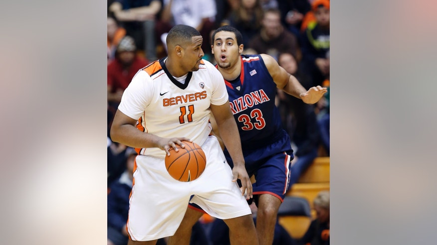 Oregon State center Joe Burton, left, drives against Arizona forward Grant Jerrett during the first half of an NCAA college basketball game in Corvallis, Ore., Saturday, Jan. 12, 2013. (AP Photo/Don Ryan)