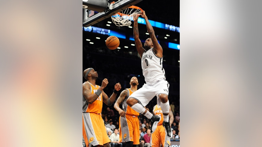 Brooklyn Nets' Andray Blatche (0) dunks a basket in front of Phoenix Suns' Jermaine O'Neal (20) and Markieff Morris, second from left, in the first half of an NBA basketball game on Friday, Jan., 11, 2013 at Barclays Center in New York. (AP Photo/Kathy Kmonicek)