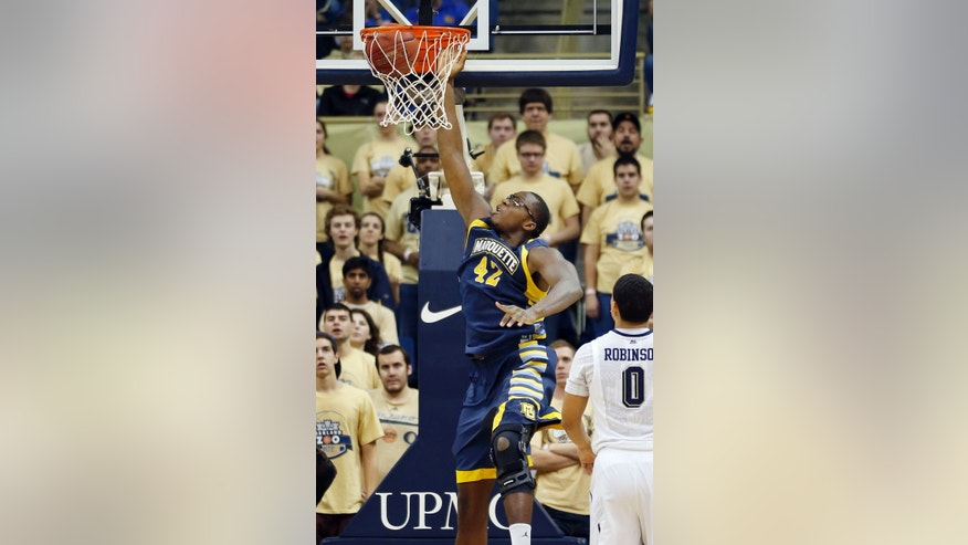 Marquette's Chris Otule (42) scores after getting past Pittsburgh's James Robinson during the first half of an NCAA college basketball game on Saturday, Jan. 12, 2013 in Pittsburgh. (AP Photo/Keith Srakocic)