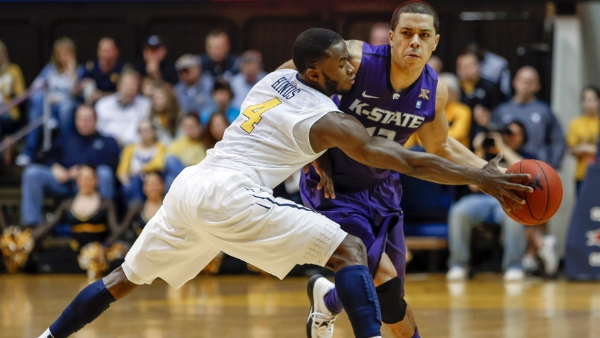 Kansas State's Angel Rodriguez, right, is defended by West Virginia's Jabarie Hinds (4) during the first half of an NCAA college basketball game at WVU Coliseum in Morgantown, W.Va., on Saturday, Jan. 12, 2013. (AP Photo/David Smith)
