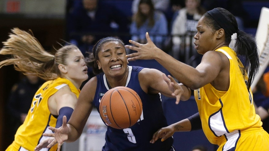Connecticut's Morgan Tuck (3) loses control of the ball as Marquette's Cristina Bigica, left, and Katie Young, right, defend in the second half of an NCAA college basketball game Saturday, Jan. 12, 2013, in Milwaukee. Connecticut won 85-51. (AP Photo/Jeffrey Phelps)