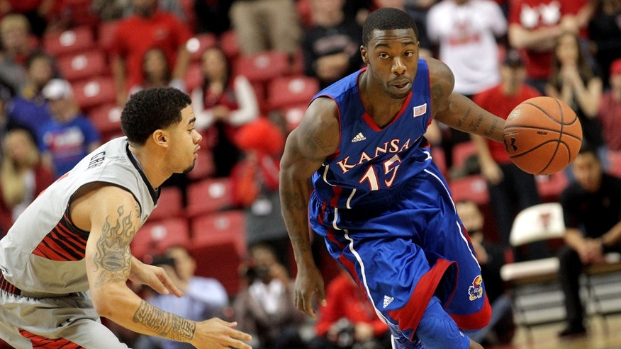 Kansas' Elijah Johnson looks to drive around Texas Tech's Josh Gray during an NCAA college basketball game in Lubbock, Texas, Saturday, Jan. 12, 2013. (AP Photo/Lubbock Avalanche-Journal,Stephen Spillman)