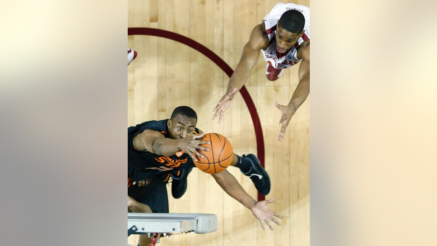 Oklahoma State guard Markel Brown, bottom, grabs a rebound in front of Oklahoma guard Cameron Clark, top, in the first half of an NCAA college basketball game in Norman, Okla., Saturday, Jan. 12, 2013. (AP Photo/Sue Ogrocki)