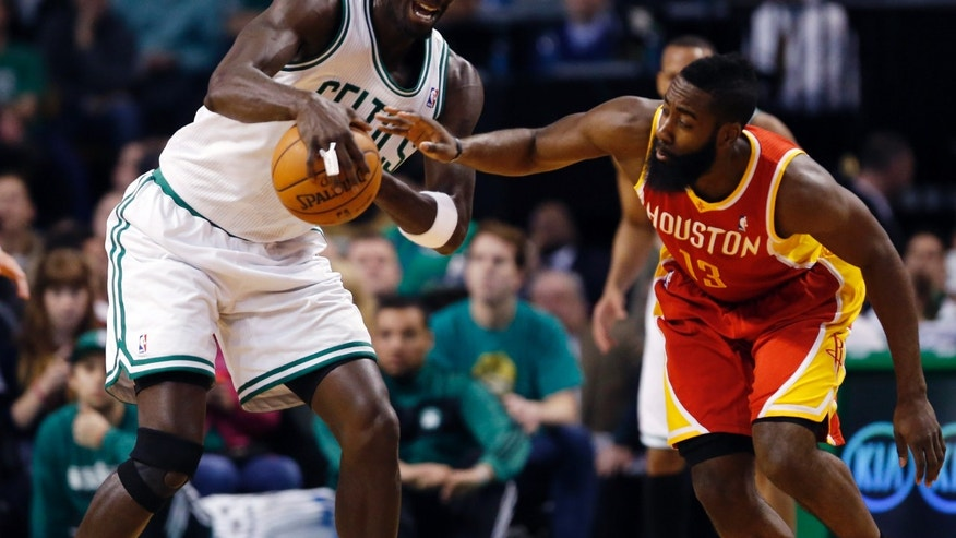 Houston Rockets' James Harden (13) tries to knock the ball from Boston Celtics' Kevin Garnett in the first quarter of an NBA basketball game in Boston, Friday, Jan. 11, 2013. (AP Photo/Michael Dwyer)