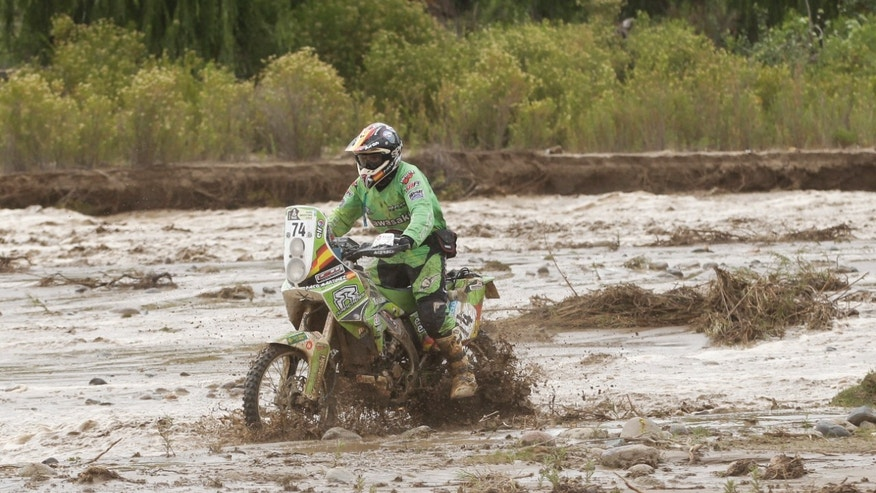 Paco Martinez of Spain rides his Kawasaki through river basin that was flooded with water rapidly due to heavy rains during the 8th stage of the 2013 Dakar Rally from Salta to Tucuman, Argentina, Saturday, Jan. 12, 2013. The 8th stage was canceled due to the flash flood. (AP Photo/Victor R. Caivano)