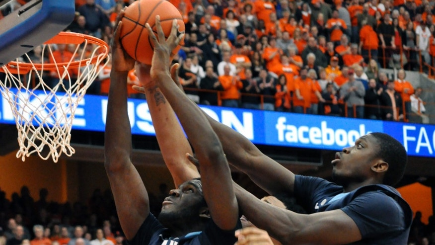 Villanova's Mouphtaou Yarou, left, grabs a rebound against Syracuse's DaJuan Coleman as Villanova's Daniel Ochefu, right, defends during the first half of an NCAA college basketball game in Syracuse, N.Y., Saturday, Jan. 12, 2013. (AP Photo/Kevin Rivoli)