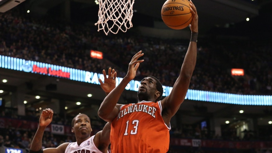 Milwaukee Bucks' Ekpe Udoh (13) scores as Toronto Raptors' Ed Davis (32) watches during first-half NBA basketball game action in Toronto, Sunday, Jan. 13, 2013. (AP Photo/The Canadian Press, Chris Young)