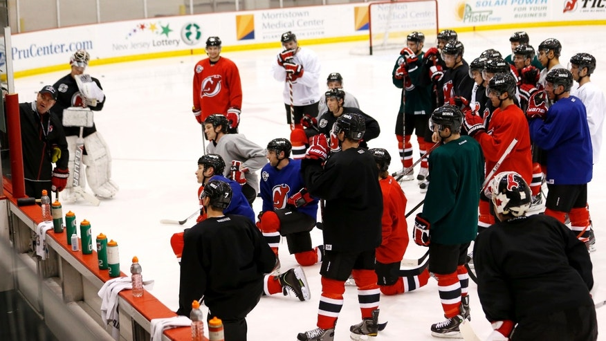 New Jersey Devils head coach Peter DeBoer, left, writes on a board during the team's first official practice since the NHL hockey lockout ended, Sunday, Jan. 13, 2013, in Newark, N.J. (AP Photo/Julio Cortez)