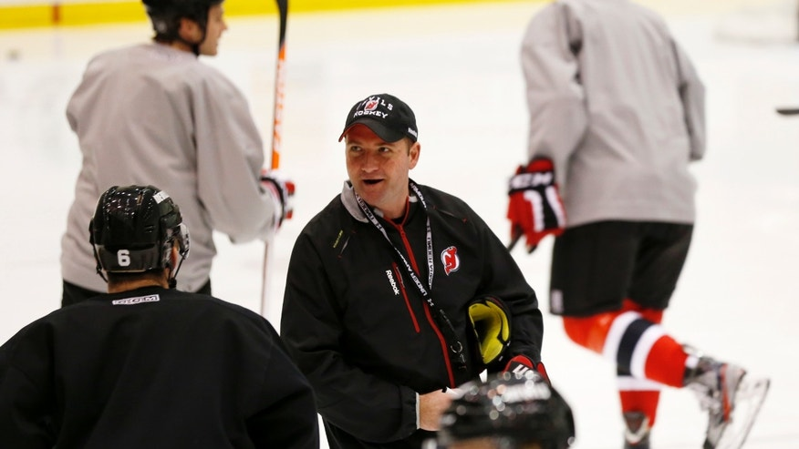 New Jersey Devils head coach Peter DeBoer, center, looks attends the team's first official practice since the NHL hockey lockout ended, Sunday, Jan. 13, 2013, in Newark, N.J. (AP Photo/Julio Cortez)
