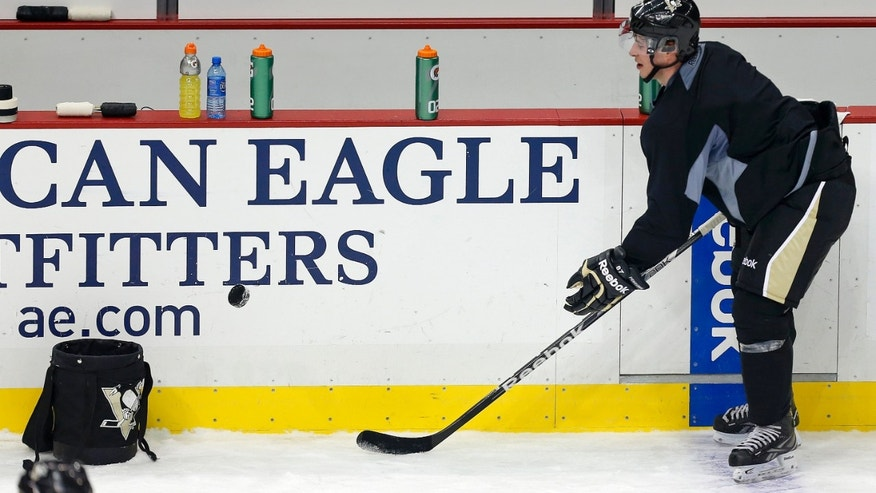 Pittsburgh Penguins' Sidney Crosby picks up pucks after an informal NHL hockey workout at the Consol Energy Center in Pittsburgh, Tuesday, Jan. 8, 2013. (AP Photo/Gene J. Puskar)
