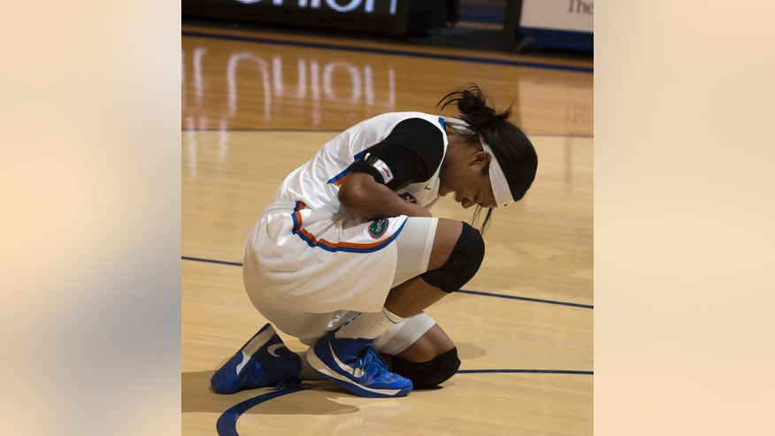 Florida forward Jennifer George (32) winces in pain after she dislocated her right shoulder during the first half of an NCAA college basketball game against Tennessee in Gainesville, Fla., Sunday, Jan. 13, 2013.  Tennessee defeated Florida 78-75. (AP Photo/Ron Irby)