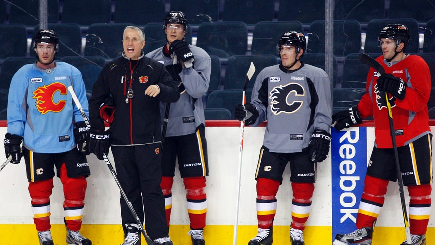 Calgary Flames head coach Bob Hartley, second from left, yells out drills as players, from left, Ben Street, Tim Jackman, Michael Cammalleri and Lee Stempniak stand by during the first day of NHL hockey training camp, Sunday, Jan. 13, 2013, in Calgary, Alberta. (AP Photo/The Canadian Press, Jeff McIntosh)