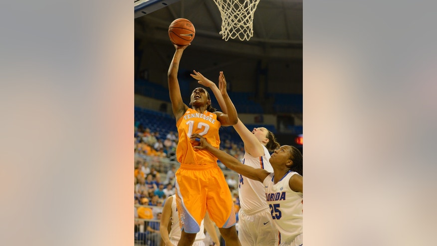 Tennessee's Bashaara Graves (12) goes for two points with Florida center Vicky McIntyre (34) and Florida forward Christin Mercer (25) try to block the shot during the first half of an NCAA college basketball game in Gainesville, Fla., Sunday, Jan. 13, 2013.  (AP Photo/Phil Sandlin)