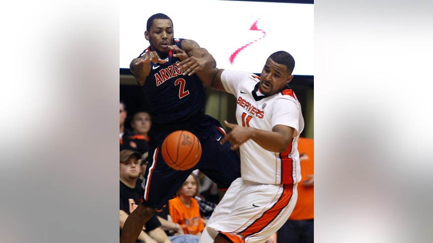 Arizona guard Mark Lyons, left, competes for a loose ball with Oregon State center Joe Burton during the second half of an NCAA college basketball game in Corvallis, Ore., Saturday, Jan. 12, 2013. Lyons scored 16 points as Arizona won 80-70. (AP Photo/Don Ryan)