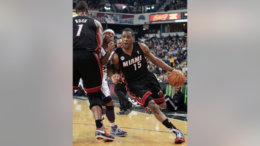 Miami Heat guard Mario Chalmers, right, uses a screen set by Chris Bosh (1) to evade Sacramento Kings guard Isaiah Thomas to drive to the basket during the third quarter of an NBA basketball game in Sacramento, Calif., Saturday, Jan. 12, 2013.  The Heat won 128-99. (AP Photo/Rich Pedroncelli)
