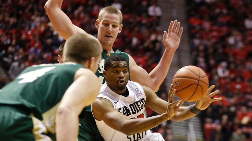 San Diego State guard Chase Tapley fires an outlet pass as he drives between Colorado State's Pierce Hornung, left, and Colton Iverson during the first half of an NCAA college basketball game Saturday Jan. 12, 2013, in San Diego. (AP Photo/Lenny Ignelzi)