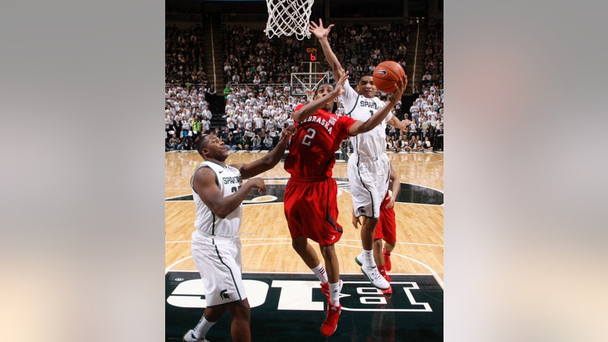 Nebraska's David Rivers (2) shoots between Michigan State's Derrick Nix, left, and Gary Harris during the second half of an NCAA college basketball game, Sunday, Jan. 13, 2013, in East Lansing, Mich. Rivers led all scorers with 18 points. Michigan State won 66-56. (AP Photo/Al Goldis)
