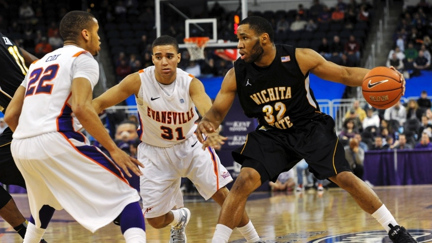 Wichita State's Tekele Cotton (32) looks to pass to a teammate as Evansville's Ned Cox (22) and D.J. Balentine (31) defend during the second half of their NCAA college basketball game, Sunday, Jan. 13, 2013, in Evansville, Ind. Evansville won 71-67. (AP Photo/Daniel R. Patmore)