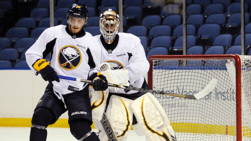 Buffalo Sabres' Mikhail Grigorenko, of Russia, gets bumped by goalie Ryan Miller in front of the crease during the first day of NHL hockey training camp in Buffalo, New York, Sunday, Jan. 13, 2013. (AP Photo/Gary Wiepert)
