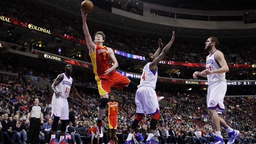 Houston Rockets' Omer Asik (3), of Turkey, goes up for a shot past Philadelphia 76ers' Dorell Wright (4) as Jrue Holiday (11) and Spencer Hawes (00) look on during the first half of an NBA basketball game, Saturday, Jan. 12, 2013, in Philadelphia. (AP Photo/Matt Slocum)