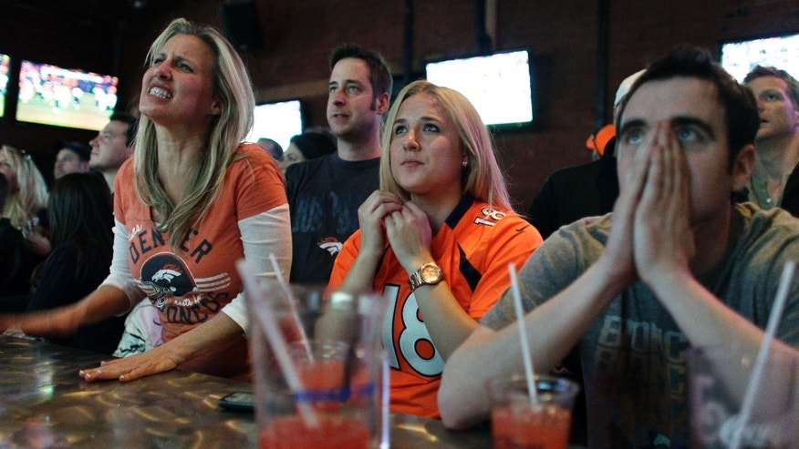 Denver Broncos fans react while watching a broadcast of the Denver Broncos failing to score against the Baltimore Ravens in overtime of an AFC divisional playoff NFL football game at Jackson's on Saturday Jan. 12, 2013, in Denver. The Ravens defeated the Broncos 38-35. (AP Photo/Brennan Linsley)