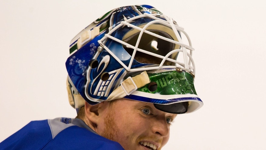 Vancouver Canucks' goalie Cory Schneider stretches during practice on the first day of the NHL hockey team's training camp in Vancouver, British Columbia Sunday Jan. 13, 2013. The team has allowed fans to attend on-ice skates during training camp. (AP Photo/THE CANADIAN PRESS/Darryl Dyck)