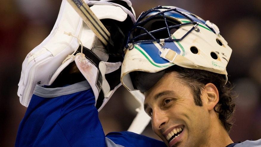 Vancouver Canucks' goalie Roberto Luongo smiles as he takes off his mask during practice on the first day of the NHL hockey team's training camp in Vancouver, British Columbia Sunday Jan. 13, 2013. The team has allowed fans to attend on-ice skates during training camp. (AP Photo/THE CANADIAN PRESS/Darryl Dyck)