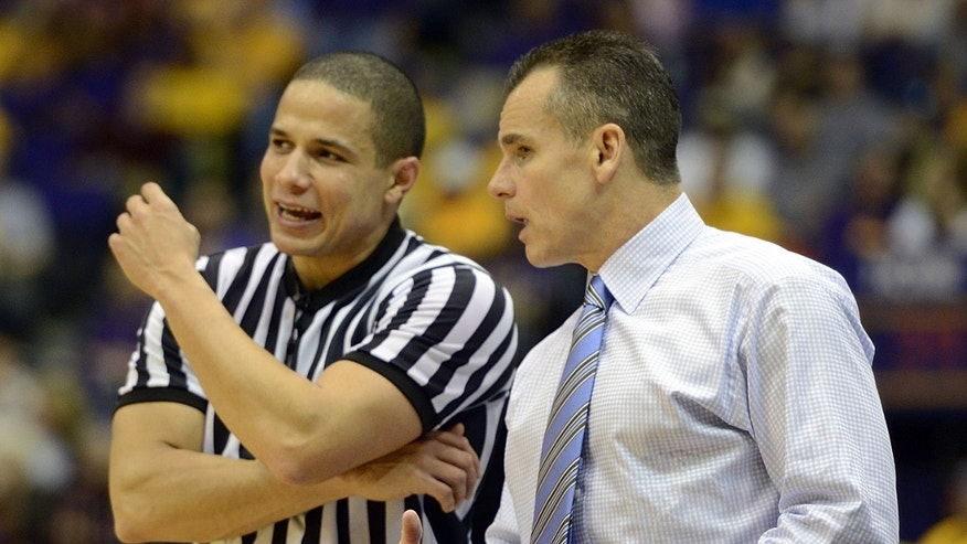 Florida head coach Billy Donovan, right, has a word with referee Steven Anderson, left, during the second half of an NCAA college basketball game at the Pete Maravich Assembly Center in Baton Rouge, La., Saturday, Jan. 12, 2013. Florida won 74-52. (AP Photo/Bill Feig)