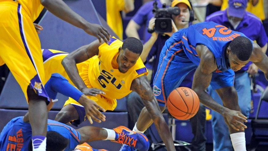 LSU forward Shavon Coleman (5) chases after a loose ball with Florida's Will Yeguete (15) and Casey Prather (24) during the first half of an NCAA college basketball game  at the Pete Maravich Assembly Center in Baton Rouge, La., Saturday, Jan. 12, 2013. (AP Photo/Bill Feig)